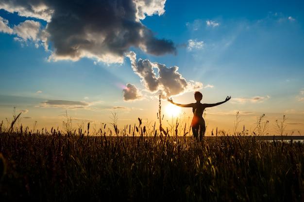 Sylwetka sportive dziewczyny ćwiczy joga w polu przy wschodem słońca.