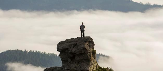 Sylwetka sportowca wspinacza na wysokiej skalistej formacji w górskiej dolinie wypełnionej białymi bufiastymi chmurami i mgłą i pokrytej wiecznie zielonymi leśnymi zboczami gór pod czystym niebem
