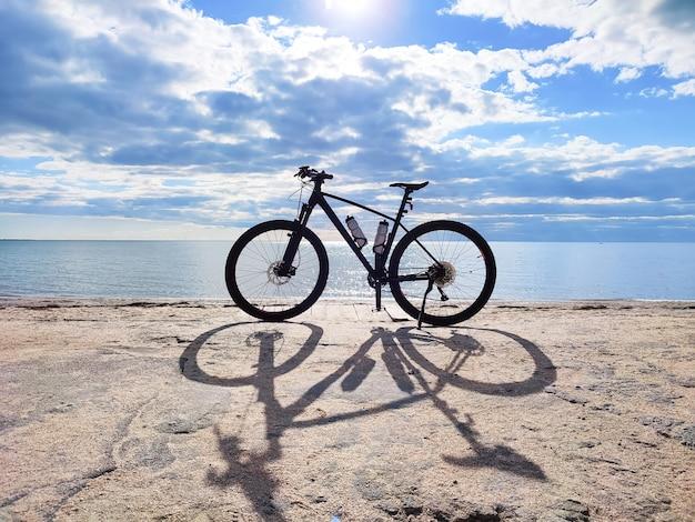 Sylwetka sportowego roweru górskiego na tle plaży