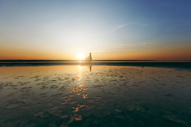 Sylwetka sportowej dziewczyny w garniturze stojącej w pobliżu roweru w wodzie o zachodzie słońca w ciepły letni dzień. koncepcja fitness.