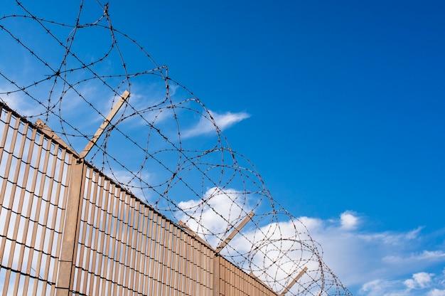 Sylwetka stalowego więzienia z drutu kolczastego na niebieskim niebie
