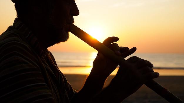 Sylwetka starszy mężczyzna gra flet bambusowy na piaszczystej plaży o zachodzie słońca