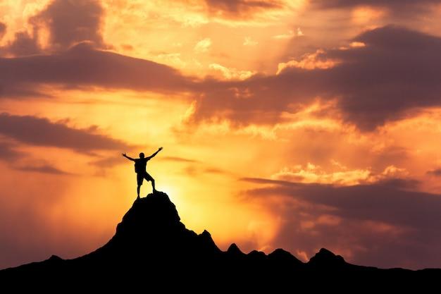 Sylwetka stojący szczęśliwy człowiek na szczycie góry