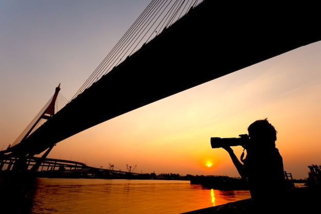Sylwetka strzał młodego chłopca robiącego zdjęcie o zachodzie słońca