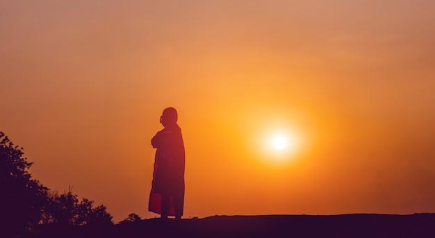 Sylwetka super bohatera chłopiec stał nieruchomo, spokojnie medytując. tylną bramę oświetla zachodzące słońce. koncepcja sylwetki