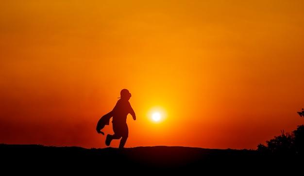 Sylwetka superbohatera pędzi naprzód z determinacją i determinacją. jogging ze słońcem w tle, koncepcja sylwetki i wieczorne bieganie
