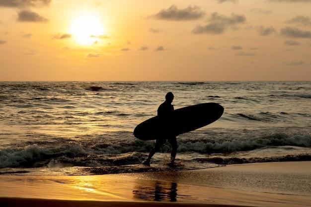 Sylwetka surfer z oceanu o zachodzie słońca