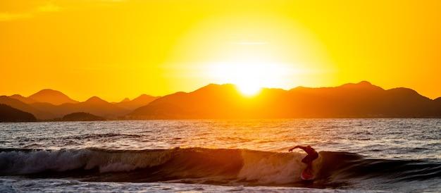 Sylwetka surfera ujeżdżającego fale podczas zachodu słońca w brazylii