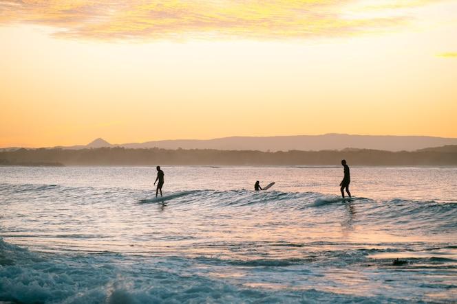Sylwetka surferów na fali o zachodzie słońca w noosa, queensland, australia