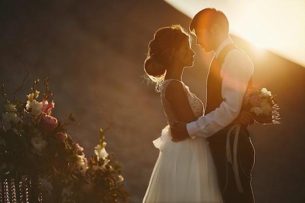 Sylwetka sympatie o zachodzie słońca. piękna i modna brunetka modelka z fryzurą modelki w białej koronkowej sukience pozuje o zachodzie słońca z przystojnymi mężczyznami w stylowej kamizelce i białej koszuli