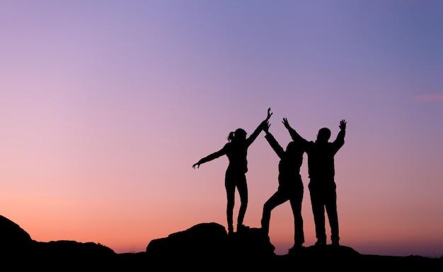 Sylwetka szczęścia rodziny z podniesionymi rękami
