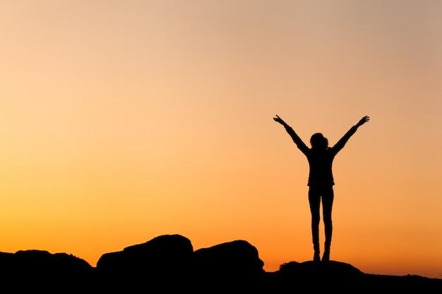 Sylwetka szczęśliwa młoda kobieta przeciw pięknemu kolorowemu niebu