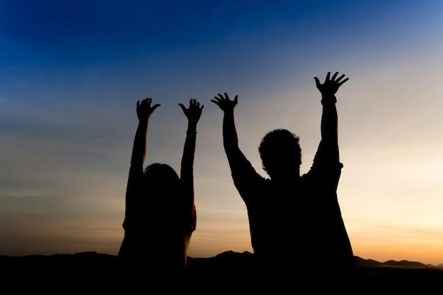 Sylwetka szczęśliwa para na tle zmierzchu nieba