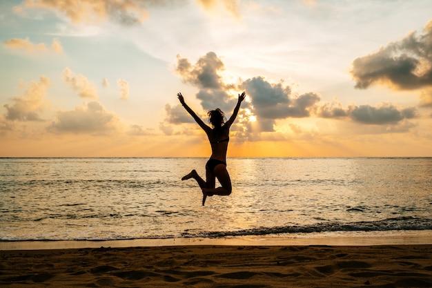 Sylwetka szczęśliwa radosna kobieta skoki na plaży przed zachodem słońca
