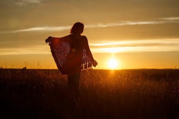 Sylwetka szczęśliwej młodej kobiety o zachodzie słońca, plenerowa dziewczyna w ponczo w kratę na polu z kłoskami