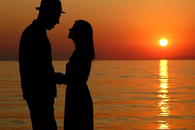 Sylwetka szczęśliwej pary kochającej się o zachodzie słońca nad brzegiem morza w grecji