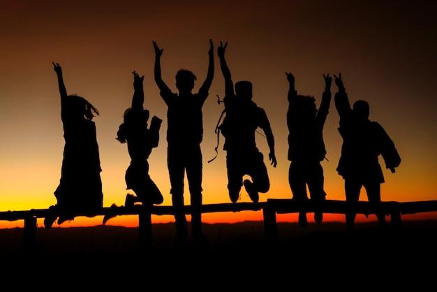 Sylwetka szczęśliwi przyjaciele skaczący na szczyt góry o wschodzie słońca