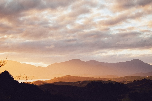 Sylwetka szeregu pięknych gór pod zapierającym dech w piersiach niebem słońca