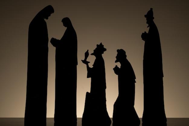 Sylwetka szopki z dzieciątkiem jezus na kolanach marii, z józefem i trzema mędrcami