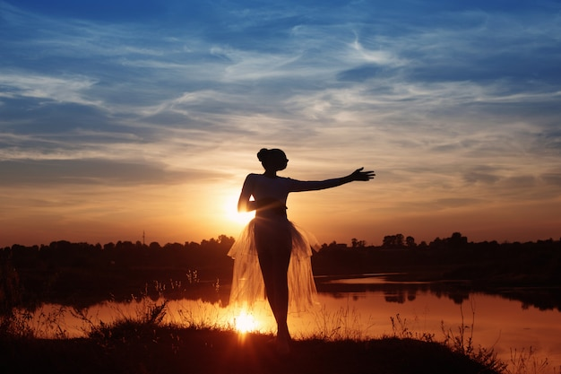Sylwetka tancerza baletowego o zachodzie słońca na zewnątrz