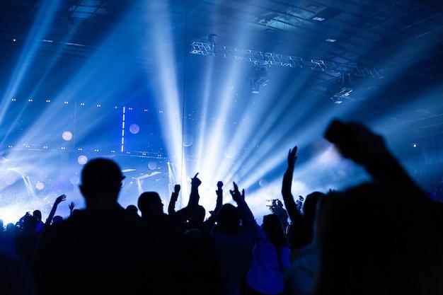 Sylwetka tłumu na koncercie. publiczność spogląda w stronę sceny. imprezowicze na koncercie rockowym. impreza muzyczna. pokaz muzyczny. sylwetka grupy. młoda publiczność.