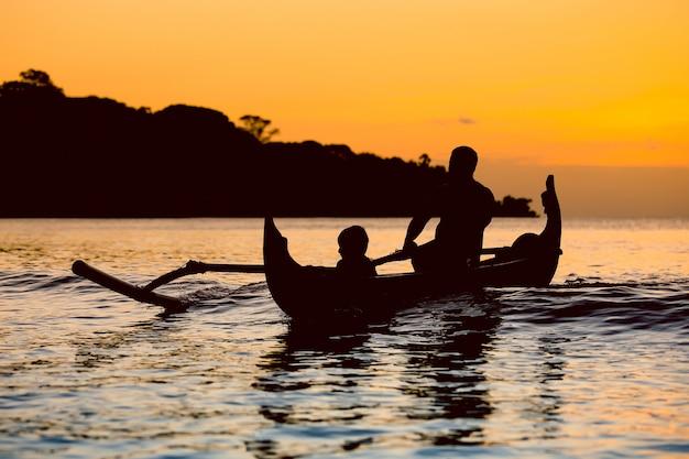 Sylwetka tradycyjna łódź rybacka przy zmierzchem w bali, jimbaran plaża