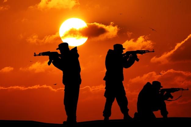 Sylwetka trzy żołnierza z broniami przy zmierzchem