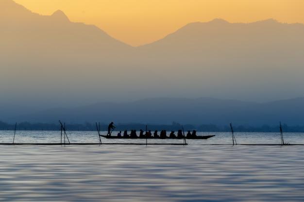 Sylwetka turyści na drewnianej łodzi przy phayao jeziorem, tajlandia.