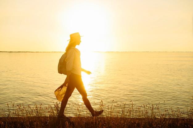 Sylwetka turysta kobieta z plecakiem spacery wzdłuż morza o zachodzie słońca sam. letnia koncepcja podróży i przygody