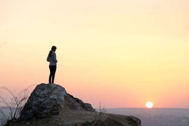 Sylwetka turysty kobieta stojąca samotnie na dużym kamieniu o zachodzie słońca w górach.