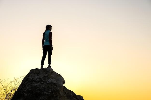 Sylwetka turysty kobieta stojąca samotnie na dużym kamieniu o zachodzie słońca w górach