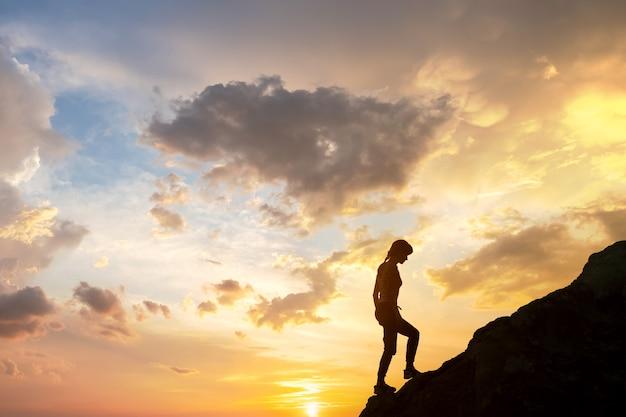 Sylwetka turysty kobieta wspinaczka na duży kamień o zachodzie słońca w górach. kobieta turysta na wysokiej skale w przyrodzie wieczorem. turystyka, podróże i pojęcie zdrowego stylu życia.