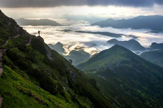Sylwetka turysty z plecakiem na skalistym zboczu góry z podniesionymi rękami