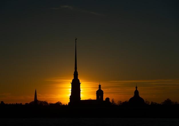 Sylwetka twierdzy piotra i pawła w sankt petersburgu w promieniach zachodzącego słońca na żółtym, pomarańczowym i czerwonym tle nieba