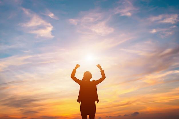 Sylwetka udanego interesu. trzymaj ręce nad głową z radością o zachodzie słońca.