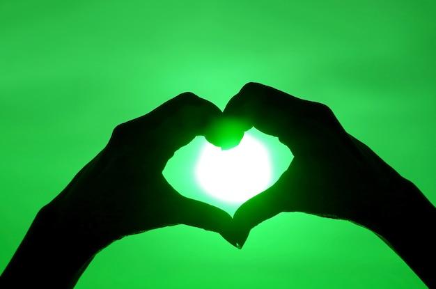 Sylwetka w stylu pop-art kobiecej ręki pozowanie znak serca przed błyszczącym słońcem na zielonym niebie
