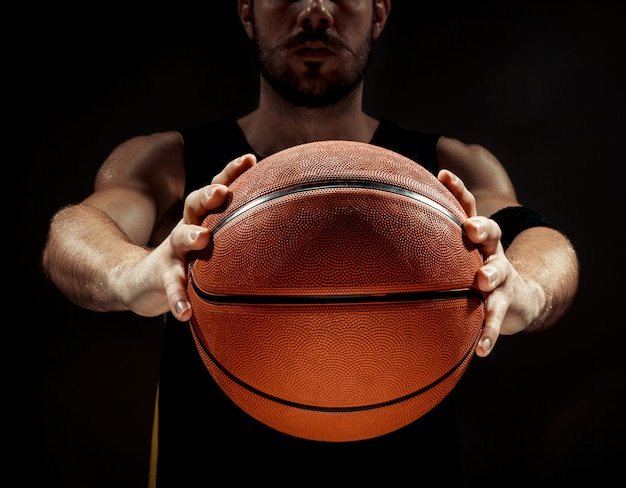 Sylwetka widok gracza koszykówki mienia koszykowa piłka na czarnym tle