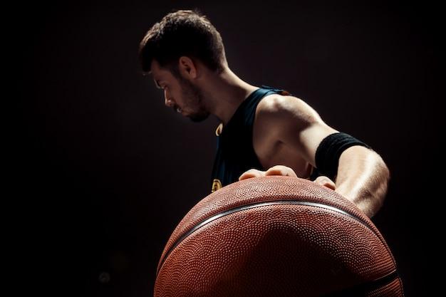 Sylwetka widok gracza koszykówki mienia koszykowa piłka na czerni ścianie