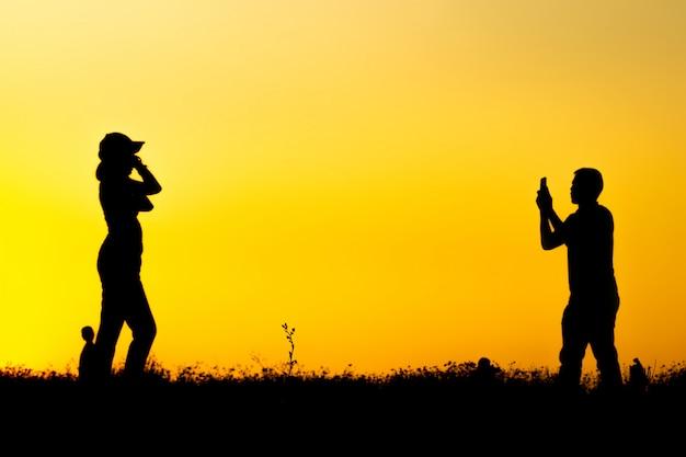 Sylwetka wielu turystów robi zdjęcia smartfonem na szczycie góry w czasie zachodu słońca.