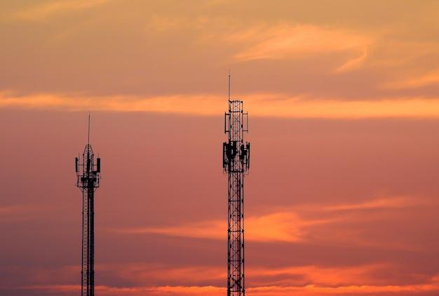 Sylwetka wieża telekomunikacyjna o zachodzie słońca.
