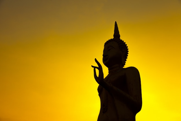 Sylwetka wizerunek buddha na złotym zmierzchu niebie