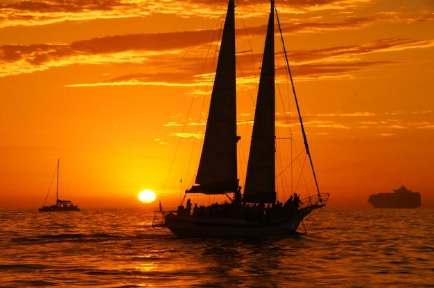 Sylwetka żaglówek na oceanie o zachodzie słońca