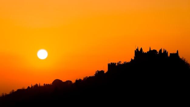 Sylwetka zamku o zachodzie słońca włoskiej panoramy z marostica orange sky