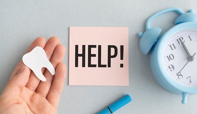 Sylwetka zęba na dłoni z napisem: pomoc i budzik.
