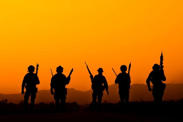 Sylwetka zespołu żołnierza w niebo zachód słońca. żołnierz z patrolowaniem karabinu maszynowego