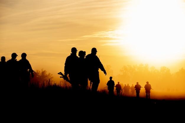 Sylwetka żołnierzy akcji chodzących trzymających broń to dym i zachód słońca, a balans bieli to efekt ciemnej sztuki