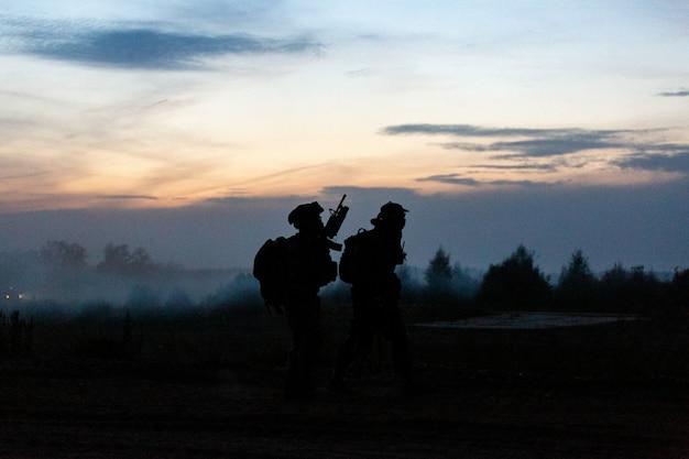 Sylwetka żołnierzy akcji chodzenia trzymać broń w tle jest dym i zachód słońca i balans bieli statek efekt ciemnej sztuki stylu