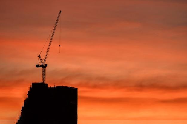 Sylwetka żuraw i budynek budowy o zmierzchu
