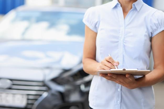 Sylwetki agenta ubezpieczeniowego ze schowkiem i długopisem na tle zepsutego wypełniania samochodu