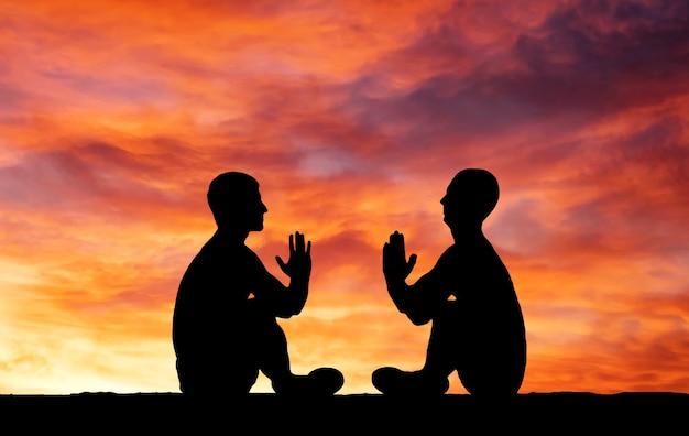 Sylwetki dwóch modlących się osób na ognistym pomarańczowym tle